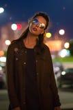 Mujer joven hermosa que se coloca en la calle iluminada en la noche Imagenes de archivo