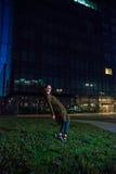 Mujer joven hermosa que se coloca en la calle iluminada en la noche Foto de archivo libre de regalías