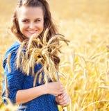 Mujer joven hermosa que se coloca en un campo de oro del trigo foto de archivo libre de regalías