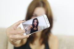 Mujer joven hermosa que se fotografía con el teléfono en casa Imagen de archivo