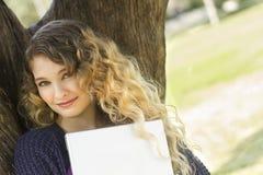 Mujer joven hermosa que se inclina contra un árbol Foto de archivo