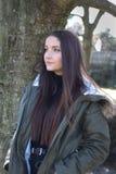 Mujer joven hermosa que se inclina contra un árbol Imagenes de archivo