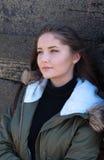 Mujer joven hermosa que se inclina contra una cerca de madera Imagen de archivo