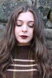 Mujer joven hermosa que se inclina en una pared de piedra Imagen de archivo libre de regalías
