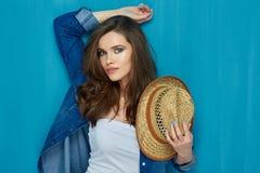 Mujer joven hermosa que se opone a la pared azul Fotos de archivo