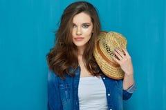 Mujer joven hermosa que se opone a la pared azul Imagenes de archivo