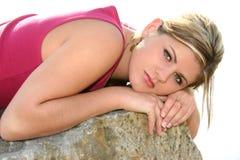 Mujer joven hermosa que se reclina sobre una roca grande fotografía de archivo libre de regalías