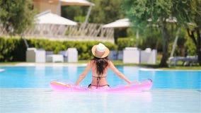 Mujer joven hermosa que se relaja en piscina almacen de video