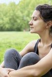 Mujer joven hermosa que se relaja en un campo verde Foto de archivo