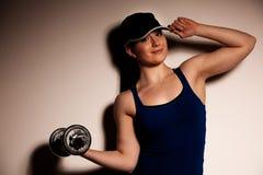 Mujer joven hermosa que se resuelve con los dumbels en gimnasio de la aptitud Fotografía de archivo libre de regalías