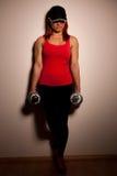 Mujer joven hermosa que se resuelve con los dumbels en gimnasio de la aptitud Foto de archivo