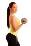 Mujer joven hermosa que se resuelve con los dumbels en gimnasio de la aptitud Imagen de archivo
