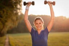 Mujer joven hermosa que se resuelve con pesas de gimnasia imágenes de archivo libres de regalías