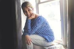 Mujer joven hermosa que se sienta cerca de ventana Imágenes de archivo libres de regalías