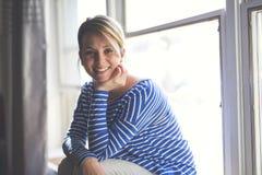 Mujer joven hermosa que se sienta cerca de ventana Fotos de archivo