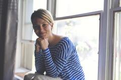 Mujer joven hermosa que se sienta cerca de ventana Imagen de archivo