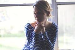 Mujer joven hermosa que se sienta cerca de ventana Foto de archivo
