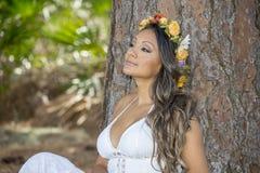 Mujer joven hermosa que se sienta contra un árbol Fotos de archivo