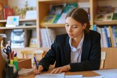 Mujer joven hermosa que se sienta en el escritorio con los papeles fotografía de archivo libre de regalías