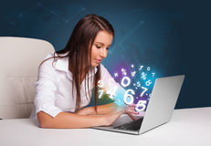 Mujer joven hermosa que se sienta en el escritorio y que pulsa en la computadora portátil con Fotos de archivo