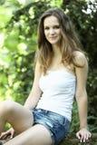 Mujer joven hermosa que se sienta en el jardín Foto de archivo
