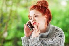 Mujer joven hermosa que se sienta en el jardín que tiene una conversación en su teléfono celular Imágenes de archivo libres de regalías
