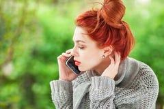 Mujer joven hermosa que se sienta en el jardín que tiene una conversación en su teléfono celular Foto de archivo libre de regalías