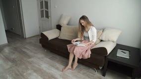 Mujer joven hermosa que se sienta en el libro y la sonrisa de lectura del sofá almacen de metraje de vídeo
