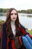 Mujer joven hermosa que se sienta en el parque con el lago en backgroun Foto de archivo libre de regalías