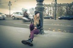 Mujer joven hermosa que se sienta en el pavimento Fotos de archivo