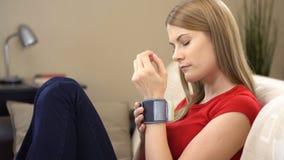 Mujer joven hermosa que se sienta en el sofá con un tonometer de la muñeca y que comprueba su presión arterial almacen de metraje de vídeo