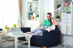 Mujer joven hermosa que se sienta en el sofá y la lectura Fotos de archivo