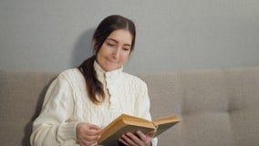 Mujer joven hermosa que se sienta en el sofá y el libro de lectura en casa almacen de metraje de vídeo