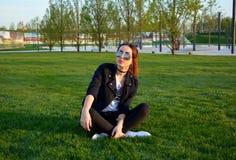 Mujer joven hermosa que se sienta en la hierba verde al aire libre Imágenes de archivo libres de regalías