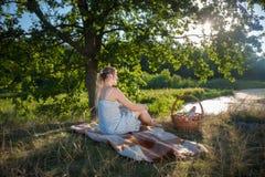 Mujer joven hermosa que se sienta en la manta debajo de árbol grande cerca del lago y que mira puesta del sol Imagen de archivo libre de regalías