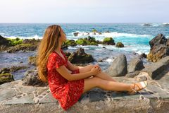Mujer joven hermosa que se sienta en la pared que goza del viento en su cara con paisaje marino imponente en Puerto de la Cruz, T imagenes de archivo