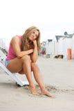 Mujer joven hermosa que se sienta en la playa con el barefeet en arena Foto de archivo