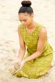 Mujer joven hermosa que se sienta en la playa con la arena que fluye de las manos Imagen de archivo libre de regalías
