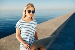 Mujer joven hermosa que se sienta en la playa con la sonrisa del ordenador portátil y c foto de archivo