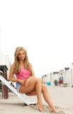Mujer joven hermosa que se sienta en la playa con pantalones cortos Foto de archivo libre de regalías