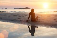 Mujer joven hermosa que se sienta en la playa en el sol poniente Foto de archivo libre de regalías