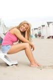 Mujer joven hermosa que se sienta en la playa y la risa Fotos de archivo