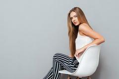 Mujer joven hermosa que se sienta en la silla aislada Fotos de archivo libres de regalías