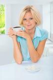 Mujer joven hermosa que se sienta en la tabla que sostiene la taza de café y Imagen de archivo