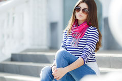 Mujer joven hermosa que se sienta en las escaleras Imágenes de archivo libres de regalías