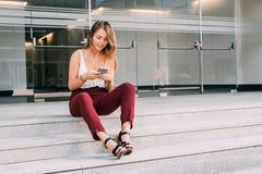 Mujer joven hermosa que se sienta en las escaleras en el teléfono móvil Fotografía de archivo