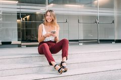 Mujer joven hermosa que se sienta en las escaleras en el teléfono móvil Imagenes de archivo