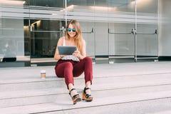 Mujer joven hermosa que se sienta en las escaleras en el wearin de la tableta Foto de archivo