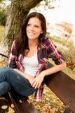 Mujer joven hermosa que se sienta en parque en la caída Imágenes de archivo libres de regalías