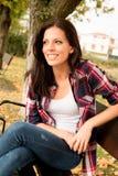 Mujer joven hermosa que se sienta en parque en la caída Foto de archivo